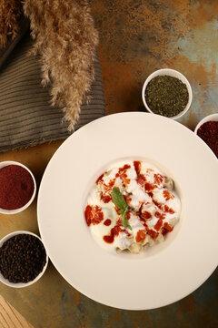 Manti, Turkish traditional ravioli on the wooden table.