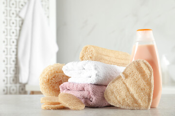 Wall Mural - Natural loofah sponges, towels and bottle with cosmetic product on table in bathroom