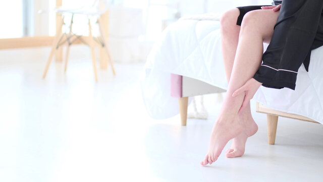 Tender woman touch her smooth and soft skin on legs, enjoy beauty procedures. young asian woman applying cream and lotion touch foot dry on bed. Copy space.