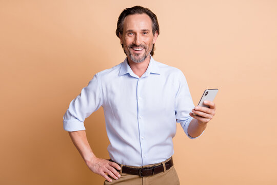 Photo of mature confident bearded guy hold telephone hand hip wear shirt isolated beige color background