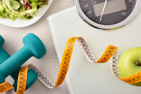 Conceptual healthy life background with dumbbell scales and healthy food
