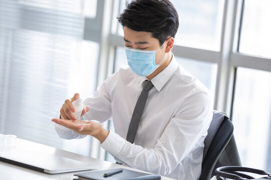 Young businessman using hand sanitizer in office