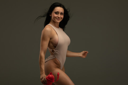 Fitness girl with shaker on a dark background.