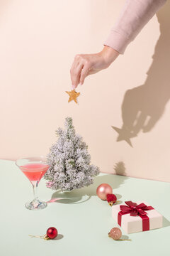 Creative arrangement against pastel orange and mint green background. Womans hand placing Christmas tree decoration. Retro aesthetic style. New Year party background.