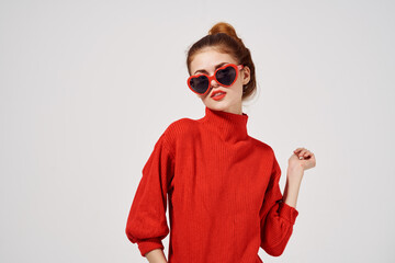 fashionable woman in sunglasses on a light background and red sweater model makeup Fotomurales