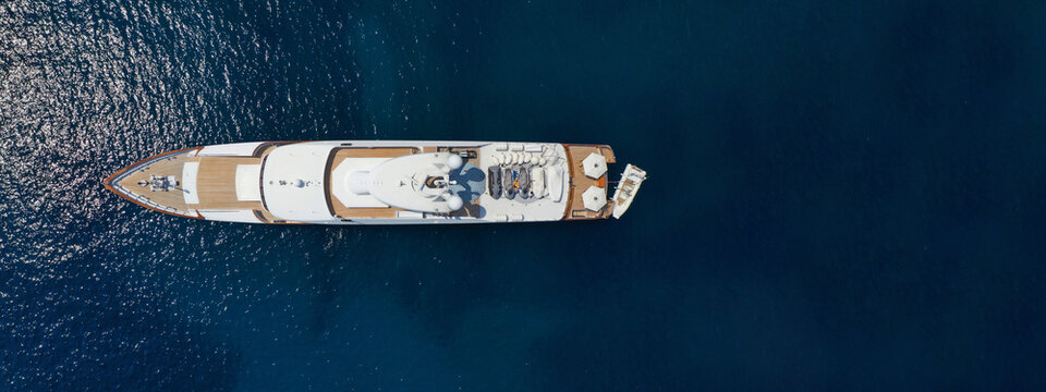 Aerial drone ultra wide photo of luxurious yacht with wooden deck anchored in deep blue Mediterranean Sea