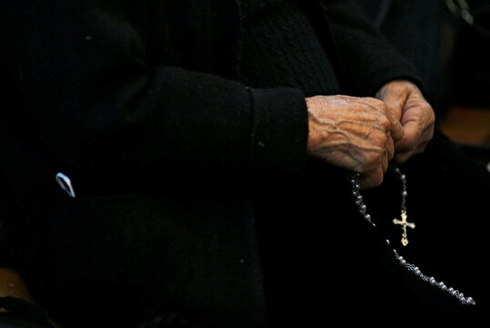 An Iraqi Christian woman prays during a mass on Christmas Eve at the Virgin Mary Church in Baghdad
