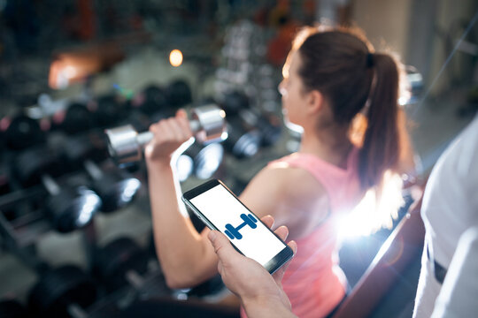 young female has personal online workout or exercising with dumbbells in gym