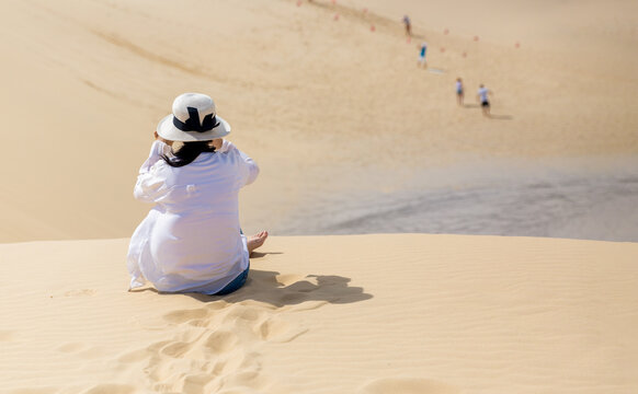 A woman taking photos of tourists sandboarding down a large sand dune.  Sandboarding is the most popular activity in Anna Bay, Australia.
