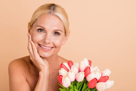 Cheerful middle aged woman enjoy her anti wrinkle tightening hold 8 march bunch isolated beige pastel color background