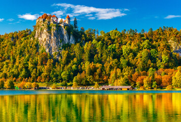 Picturesque view of Lake Bled in autumn, Slovenia. Beautiful landscape with colorful trees on the hills reflected in the water