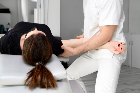 Male therapist giving massage to relief shoulder pain to a female patient in physiotheraphy clinic. High quality photo.