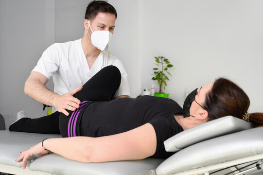 Woman lying on massage table while his physical therapist doing special exercises for physical therapy for sciatica and pinched nerve problems. High quality photo