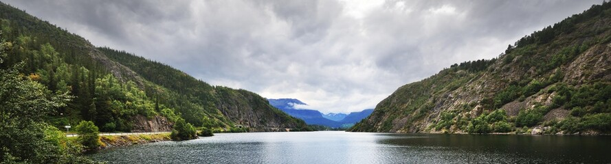 Fjord lake in the heart of Norway under the stormy sky. Dramatic cloudscape. Northern forest and...