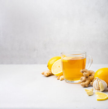 Hot herbal tea with ginger, garlic, lemon and honey vitamins C over grey background. Concept alternative medicine, natural homemade remedy for cold and flu. Support the immune system. Well-Being and