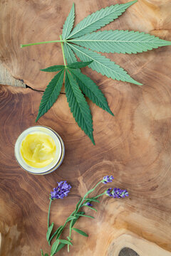 Still life detail of CBD massage lotion and cannabis leaves on a piece of rustic wood