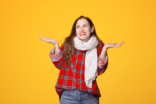 Young unsure female in casual clothes smiling and shrugging shoulders against yellow background