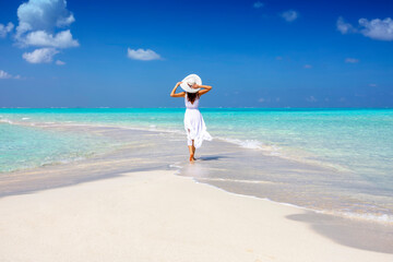 A woman in a white summer dress stands on a sandbar surrounded by turquoise ocean in the Maldives islands