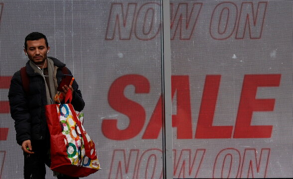 A man carries a shopping bag as he stands outside a clothing store at the start of the Boxing Day sales amid the outbreak of the coronavirus disease (COVID-19) in Manchester