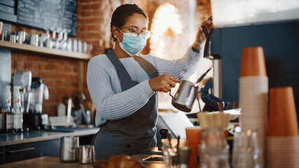 Beautiful Latin American Female Barista in Face Mask is Making a Cup of Cappuccino in Coffee Shop Bar. Social and Medical Health Restrictions Concept in a Loft-Style Cafe During Coronavirus Pandemic. - fototapety na wymiar
