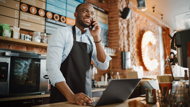 Black African American Coffee Shop Employee Accepts a Pre-Order on a Mobile Phone Call and Writes it Down on Laptop Computer in a Cafe. Restaurant Manager Browsing Internet and Talking on Smartphone.