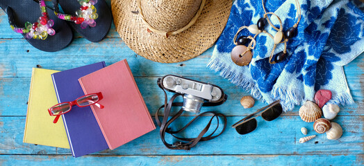 vacation and summer holidays, flat lay with books, camera, flip flops, seashells, sunglasses, beach towel, straw hat