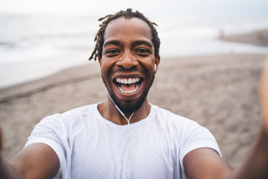 Laughing black man holding camera and taking selfie on seacoast
