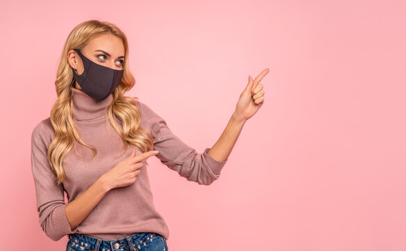 Young woman in pink blouse, sterile face mask to safe from coronavirus virus covid-19 during pandemic quarantine pointing fingers on workspace mock ups copy space isolated on pastel pink background.