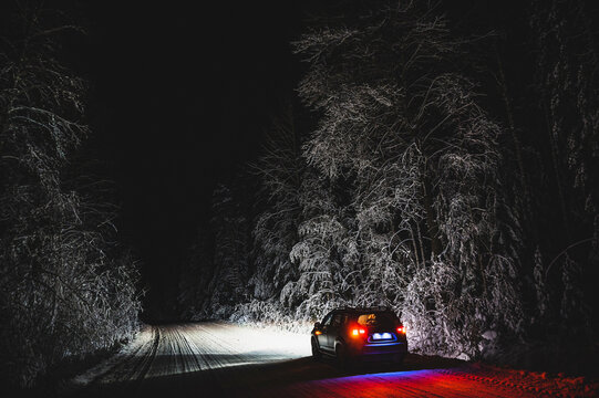 car on the night road in the winter forest