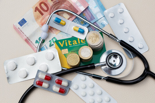 Black stethoscope, euros coins and banknotes, french vital card and packs of pills