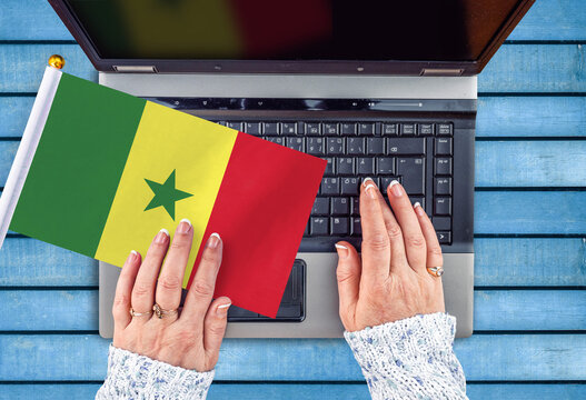 woman hands and flag of Senegal on computer, laptop keyboard