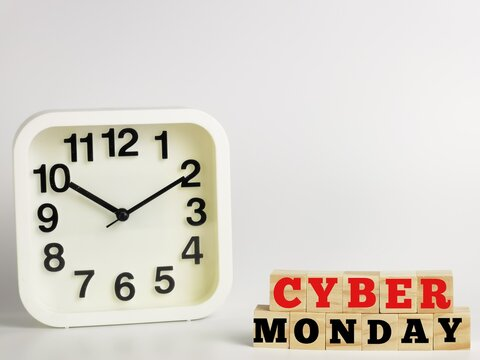 Text CYBER MONDAY on wooden cubes with alarm clock isolated on white background.Business concept.