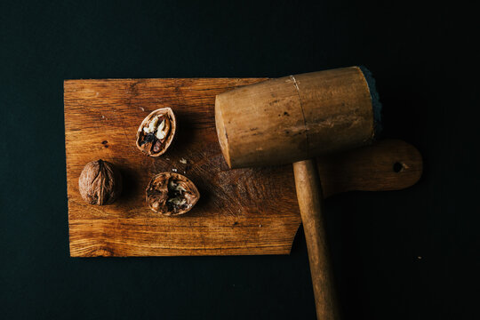 A top view of the walnut breaking process with a wooden mallet