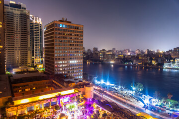 Aerial view of the city of Cairo at night along the river Nile. Skyline of the African city of Egypt Fotobehang