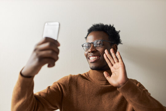 Happy joyful young Afro American male in warm sweater posing isolated with cell phone using front camera for video chat, waving hand, greeting friend with smile. People and technology concept
