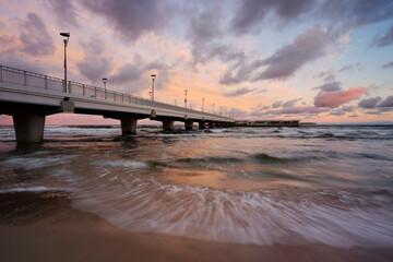 Fototapeta Molo spacerowe na wybrzeżu Morza Bałtyckiego, kolorowy wschód słońca , Kołobrzeg, Polska. obraz