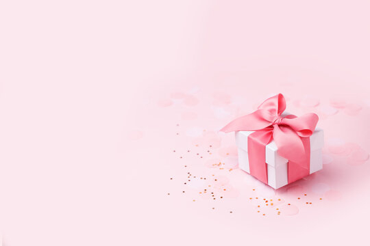 Holiday pink background with gift, white satin bow, ribbon. Valentine's Day, Happy Women's Day, Mother's Day, Birthday, Wedding, Christmas. space for text, banner, flyer