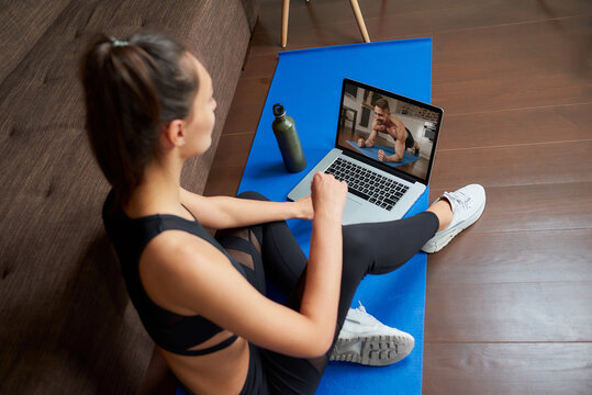 A laptop screen view over a woman's shoulder. A sporty girl in a tight suit is watching a workout video on laptop in her apartment. Woman is listening to a coach during a virtual fitness class at home