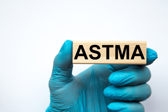 The doctor's hands show the word ASTMA . a gloved hand on a white background. Medical concept. the medicine
