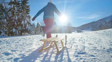 LOW ANGLE: Unrecognizable young woman runs along a snowy meadow pulling her sled Fotobehang
