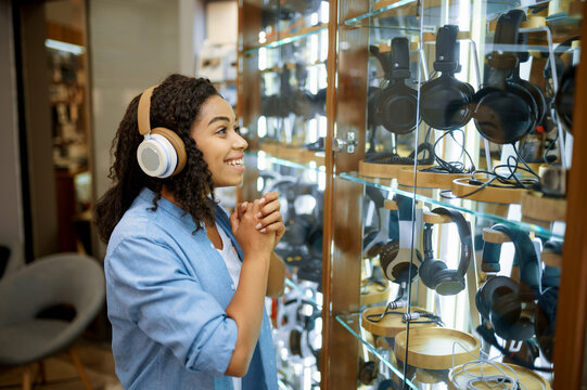 Woman trying on headphones in speaker system store