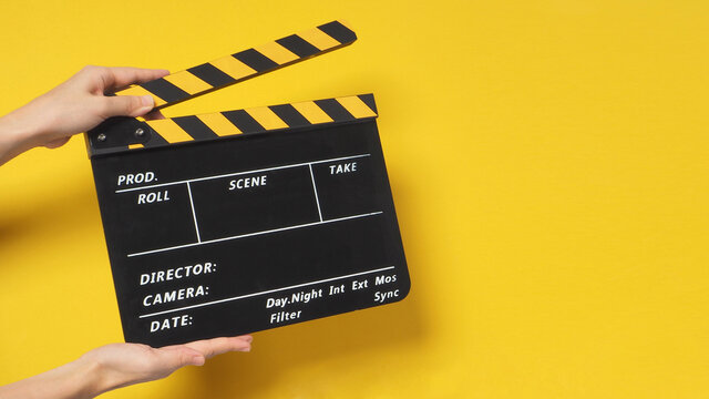 Hand is holding clapper board or movie slate.It is used in film production and cinema,movies industry on yellow background.