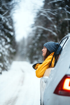 Brave woman drive by car and looking away to winter forest. Handsome girl wearing yellow jacket looking out of the car window while traveling on winter forest road.