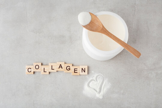 collagen powder in a spoon on a gray table, top view, heart, inscription collagen