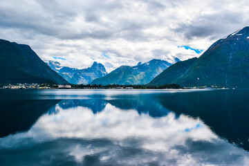 Beautiful landscape of mountains reflected in Romsdal Fjord or Romsdalsfjord in cloudy weather. More og Romsdal county. Norway.