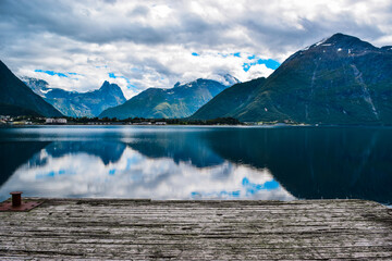 Beautiful landscape of mountains reflected in Romsdal Fjord or Romsdalsfjord in cloudy weather. Andalsnes. Norway.