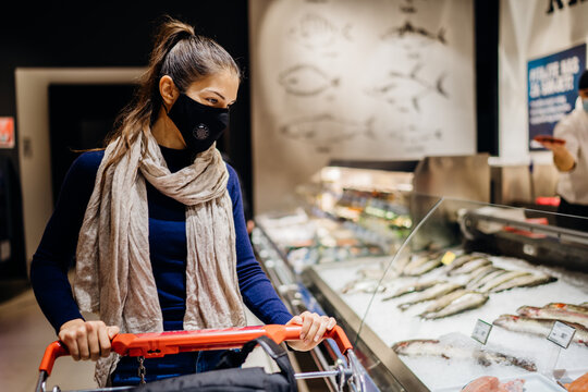 Young woman wearing protective face mask shopping in a supermarket,buying groceries.Seafood and fish shopping.Eating healthy food during coronavirus COVID - 19 pandemic.Healthy fish oils.Grocery shop