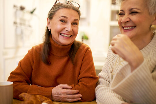 Indoor image of two joyful positive European female friends on retirement having fun, talking, telling funny jokes during meeting at home or cafe. People, friendship, age and retirement concept