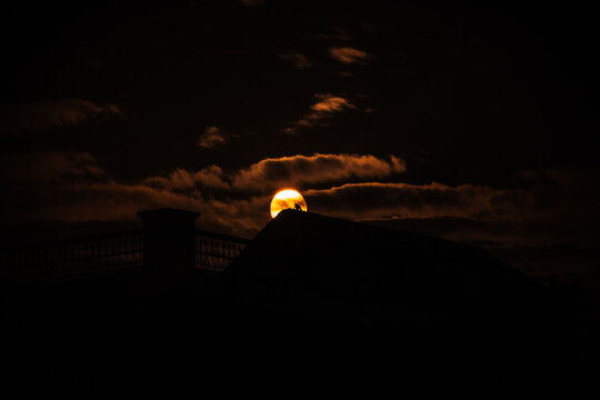The silhouettes of buildings and the sun behind the clouds