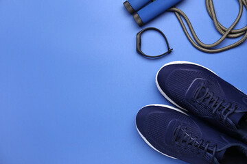 Sportive shoes and jumping rope on color background